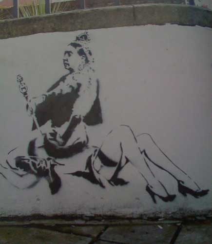 The queen sits on someone's face: graffiti by Banksy.