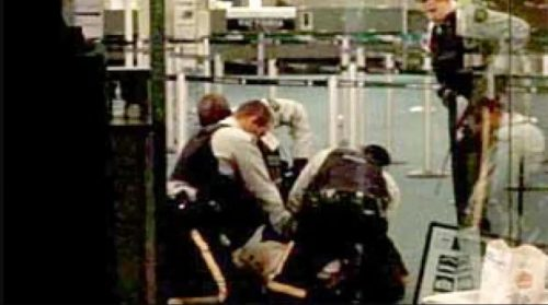 Four cops surround a man on the ground just prior to killing him in the Vancouver airport.