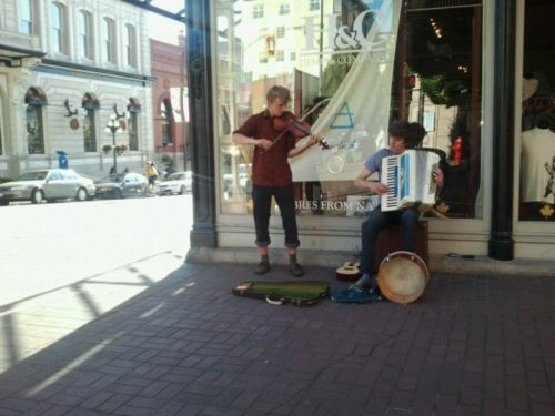 Fiddle player and accordian player perform for money on the street