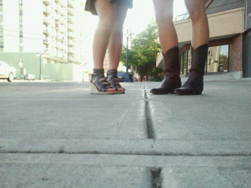 Two women stand on a sidewalk in short skirts and in cowgirl boots and shoes with straps