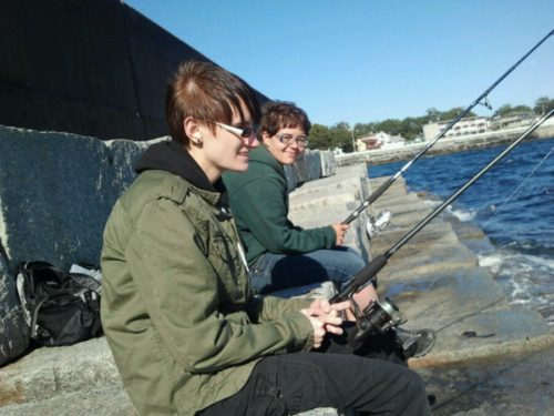 Two cool people sit on the Victoria breakwater fishing in the sunshine