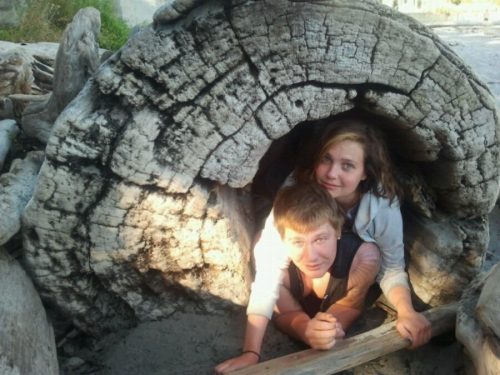 A log with a rotten core sits on the beach and Ben and Kelly are inside it