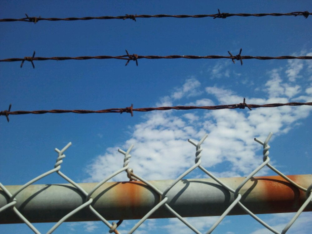 bluesky and clouds with barbed wire in foreground