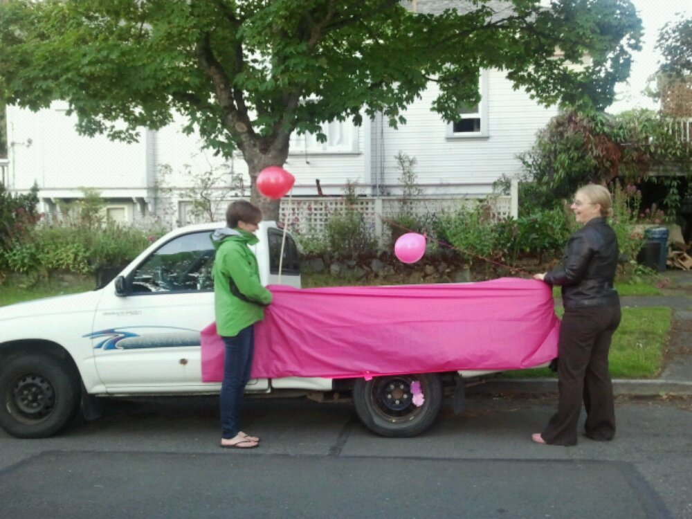 Jes and Becky hold up pink vinyl to see how it looks on the Pink Pages parade truck