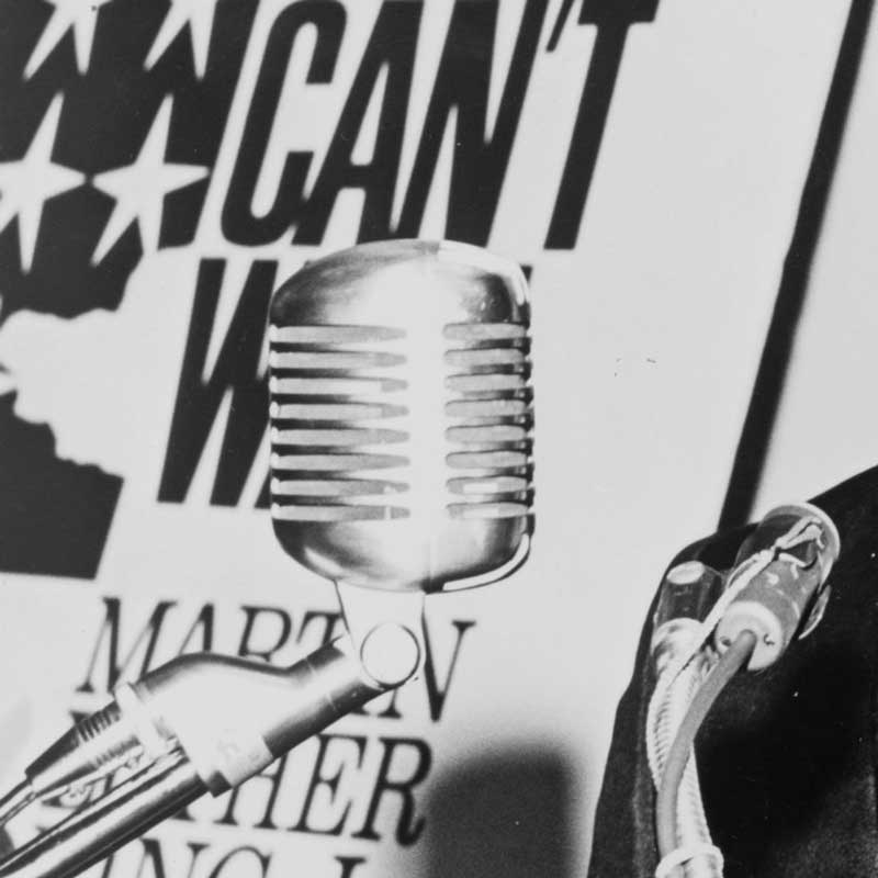 cropped image of Martin Luther King at the podium with poster in the background