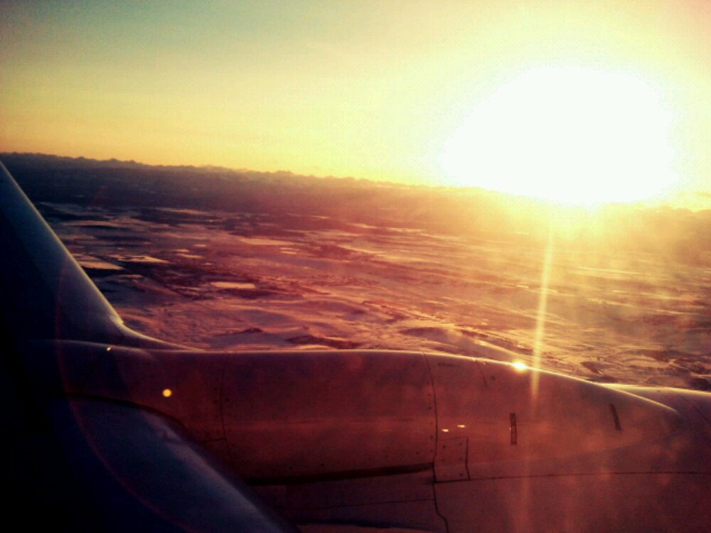 The sun sets over the Rocky Mountains as seen from a plane window