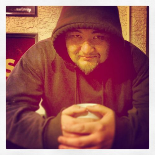 Billy puts his hoody up and holds his warm coffee on a cool night in Cook Street Village, Mocha House