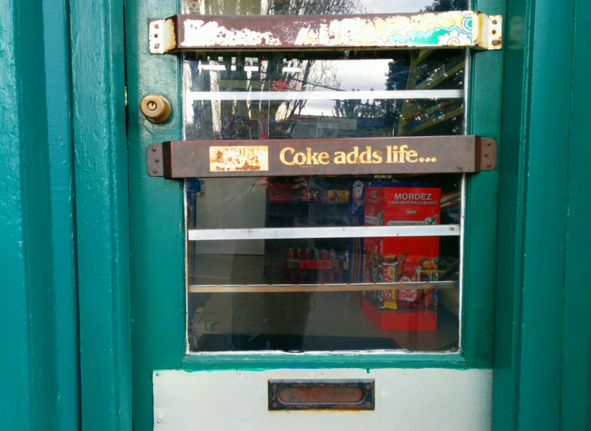 "Door to a convenience store that reads ""Coke adds life"""
