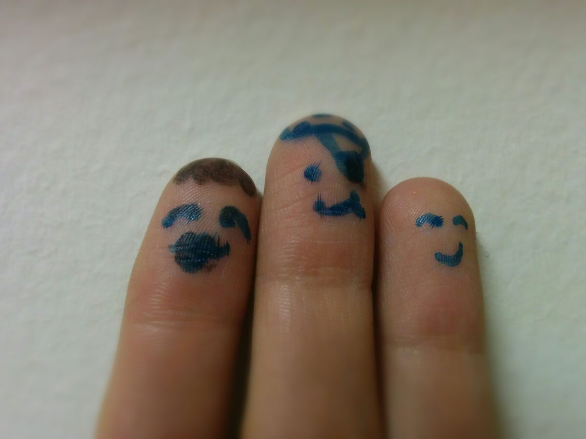 Three fingers with faces drawn on them, stand together.