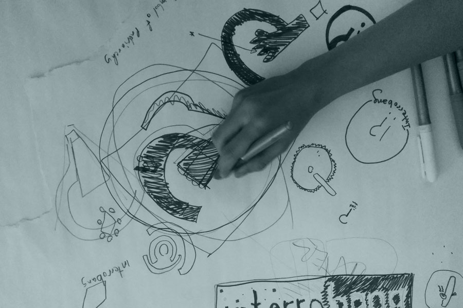 Sabrina's hand reaches out to sketch some ideas for the Interrobang logo