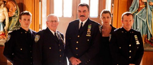 The Reagan family stand in full NYPD uniform in the light of the Catholic Church