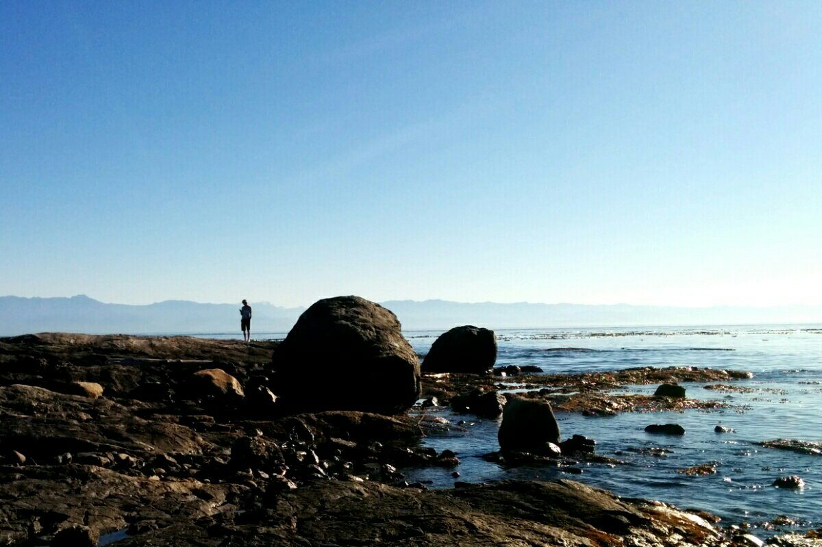 Human stands in shadow on Clover Point in the Salish Sea