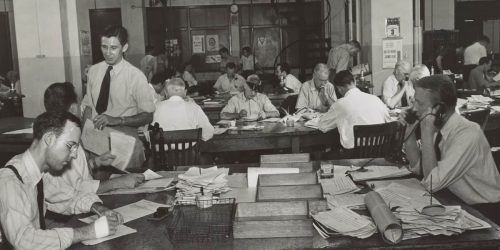 White journalists sit around a busy news room, black and white