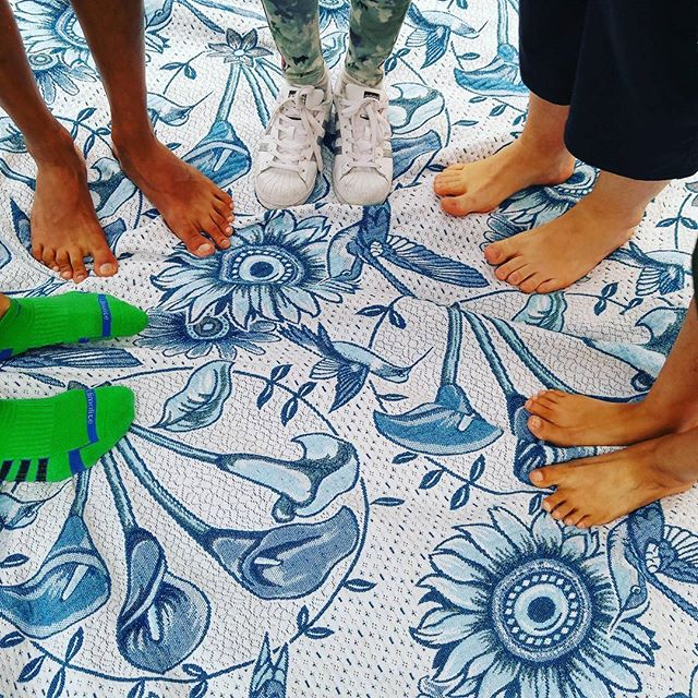 Five pairs of feet posing on a picnic blanket.