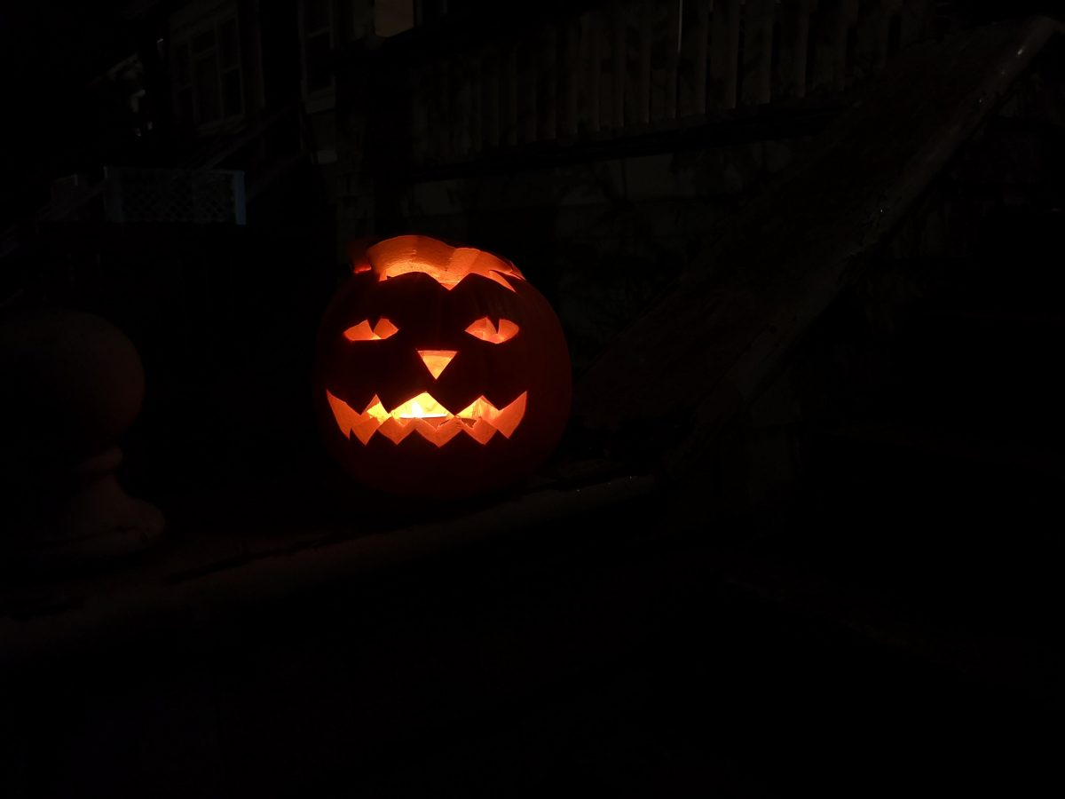 A glowing pumpkin on the banner of our front step, in VicWest.