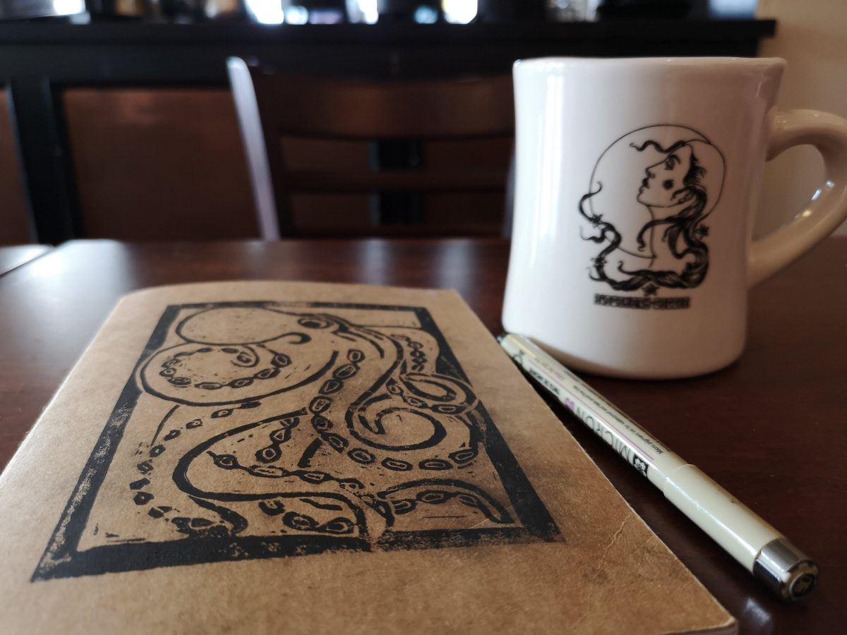 Best notebook, with a print of an octopus on the cover, sitting on the table at Discover Coffee.