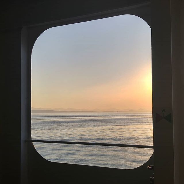 A patch of ocean and sky appear through a window on a BC Ferry.