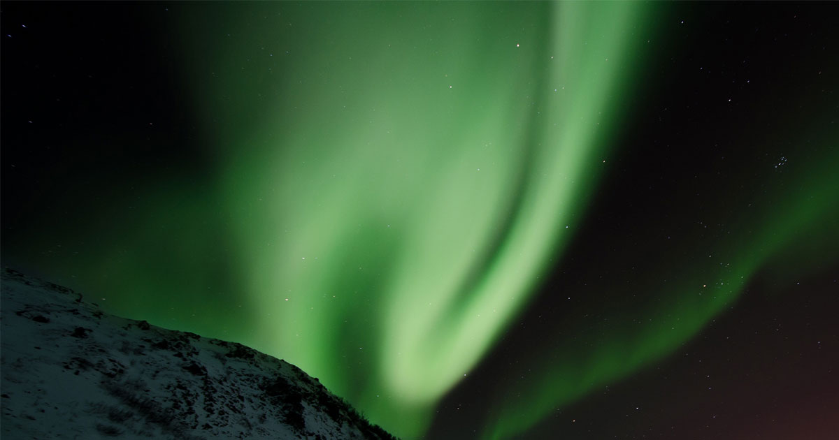 The northern lights shine at night over the snow covered hills.