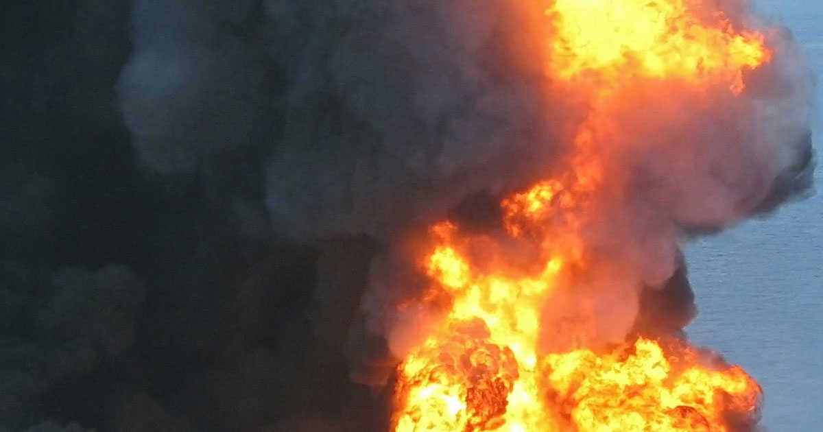 Smoke and fire rise up from a burn oil platform in the ocean.
