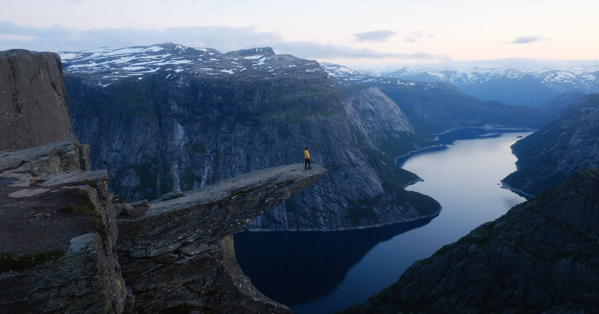 A small human stands on cliff overlooking a great divide in Norway.