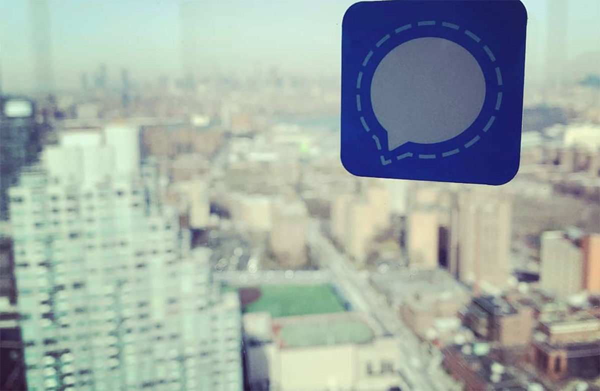The Signal app logo on a window over a city scape.